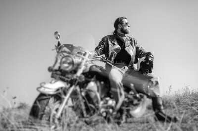 Fotomural Retrato de un hombre joven con la barba que se sienta en su motocicleta del crucero y que mira al sol. El hombre está usando chaqueta de cuero y blue jeans. Bajo punto de vista. Efecto de desenfoque d