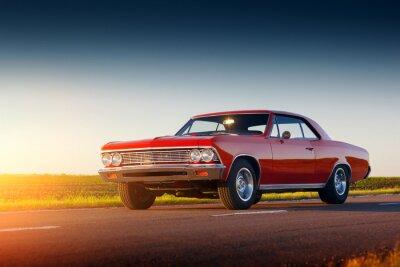 Fotomural Retro coche rojo permanecer en la carretera de asfalto en la puesta de sol