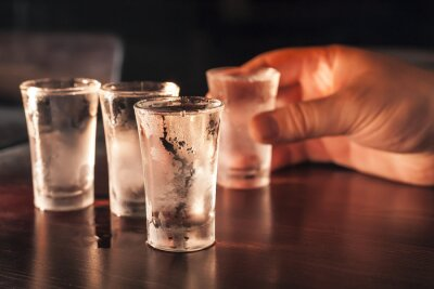 Fotomural Shot glass of vodka in hand on a wooden table.