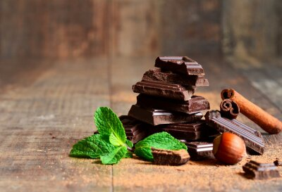 Fotomural Stack of chocolate slices with mint leaf,hazelnut and cinnamon.