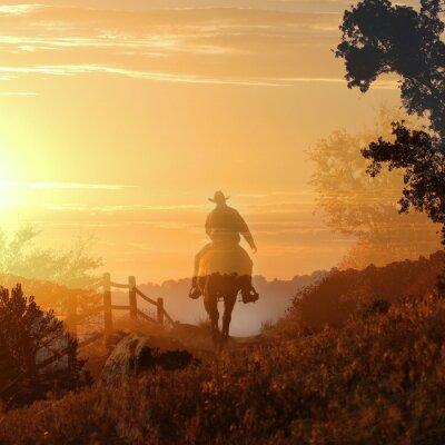 Fotomural Sunset Cowboy. Un vaquero cabalga hacia el atardecer en las capas transparentes de nubes de color naranja y amarillo, una valla y árboles.