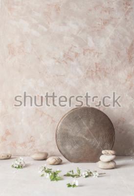 Fotomural Todavía vida con las flores, las piedras y el florero de cerámica realzado en fondo texturizado de la pared en estilo del wabi-Sabi. Enfoque selectivo