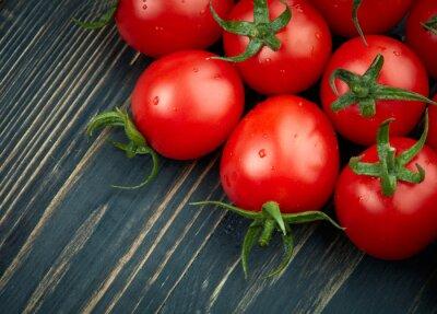 Fotomural Tomates maduros sobre fondo de madera oscura