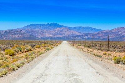 Fotomural Un camino de tierra en el Karoo que corre al lado de las cercas de la granja.