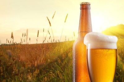 Fotomural Vaso de cerveza y una botella contra el campo de trigo y la puesta de sol