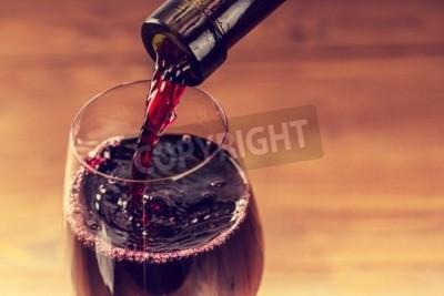 Fotomural Verter el vino tinto en el vidrio contra el fondo de madera