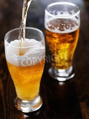 Fotomural Verter la cerveza en una taza de altura en la mesa de pizarra