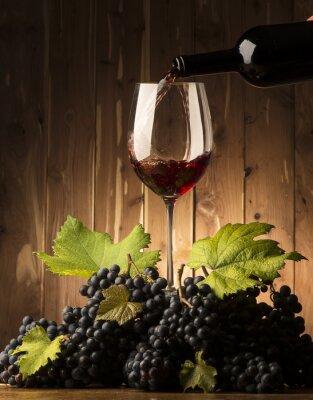 Fotomural Vidrio con vino tinto y grapeson la mesa de madera