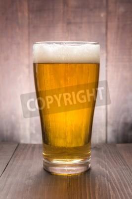 Fotomural Vidrio de cerveza en el fondo de madera.
