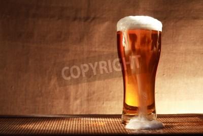 Fotomural Vidrio lleno de cerveza de la frescura con la espuma en la tabla contra el fondo gris de la lona
