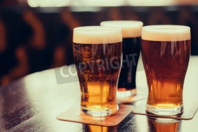 Fotomural Vidrios de cerveza ligera y oscura en un fondo del pub.