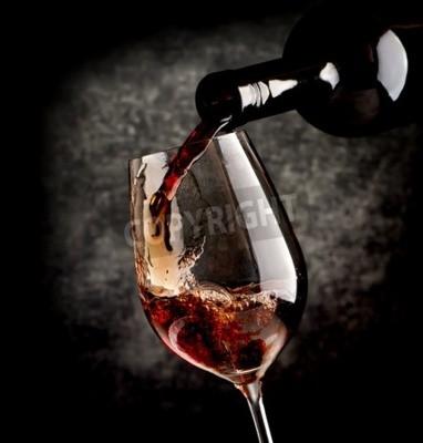 Fotomural Vino que vierte en copa de vino sobre un fondo negro
