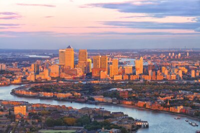 Fotomural Vista aérea del distrito financiero del este de Canary Wharf Docklands rodeado por el río Támesis, con edificios iluminados por la puesta de sol de colores
