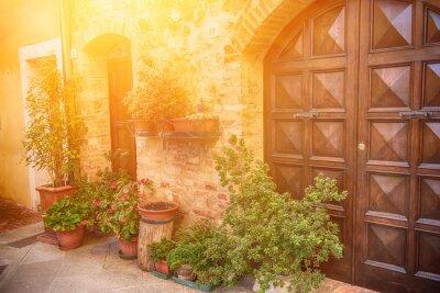 Fotomural Vista de la antigua ciudad europea antigua. Calle de Pienza, Italia, con puertas de madera. Fondo soleado del recorrido.