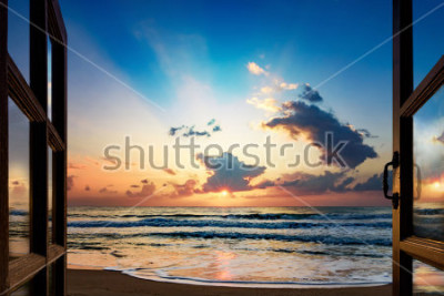 Fotomural Vista del amanecer sobre el mar desde la ventana abierta.