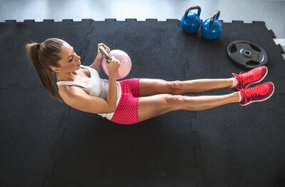 Fotomural Woman working on her abs with kettlebell