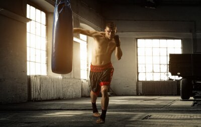 Fotomural Young man boxing workout in an old building