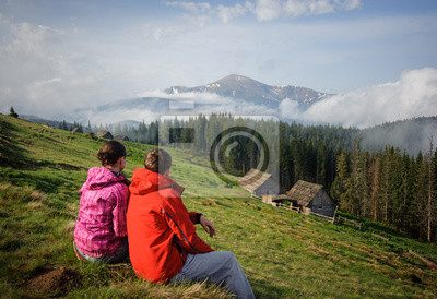 a young couple sitting on the grass enjoying views of the mounta