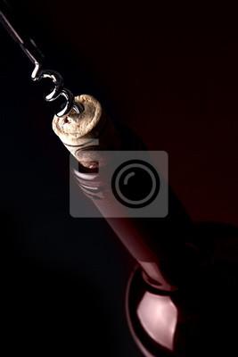Abrir una botella de vino, sobre fondo oscuro. Reflexión roja.