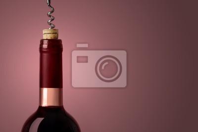 Abrir una botella de vino tinto, sobre fondo morado