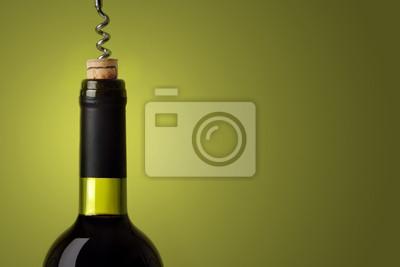 Abrir una botella de vino tinto, sobre fondo verde