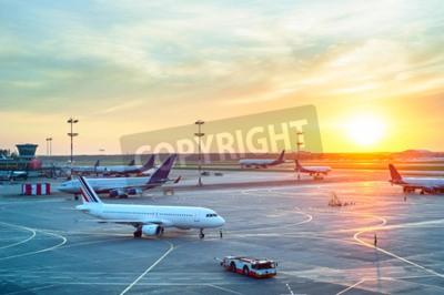 Póster Aeropuerto con muchos aviones en la hermosa puesta de sol