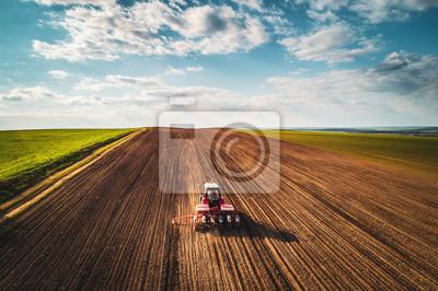 Agricultor con tractor sembrando cultivos en el campo, vista aérea