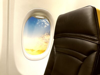 Airplane window with view on a beautiful sky