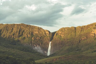 Amazing waterfall in the canyons of Minas Gerais during the sunset with clouds in the sky in Brazil