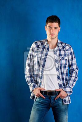 aea796ac27 Póster apuesto joven con pantalones vaqueros de mezclilla camisa a cuadros  en color azul