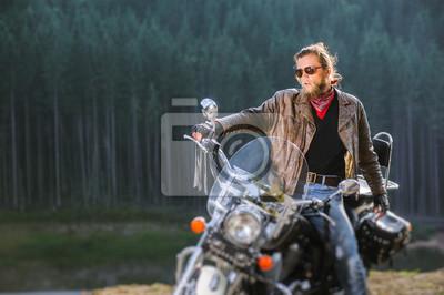 Apuesto joven motociclista está sentado en su moto de viaje de larga distancia con el bosque en el fondo. El hombre lleva chaqueta de cuero y gafas de sol. Efecto de desenfoque de la lente de cambio d