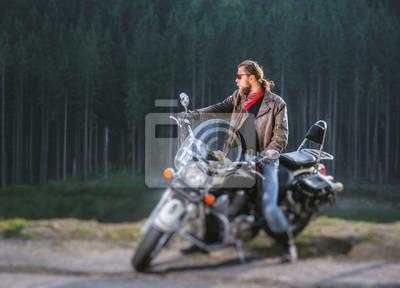 Apuesto joven motociclista está sentado en su moto de viaje de larga distancia con el bosque en el fondo. El hombre se está preparando para viajar. El hombre lleva chaqueta y gafas de sol. Efecto de d