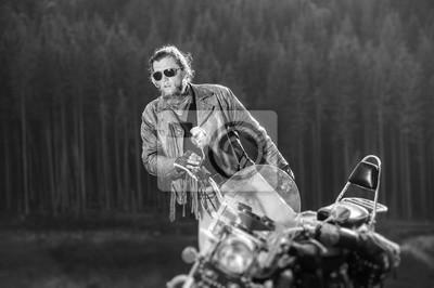 Apuesto joven motociclista grave está sentado en su moto de viaje de larga distancia con el bosque en el fondo. Efecto de desenfoque de la lente de cambio de inclinación. En blanco y negro
