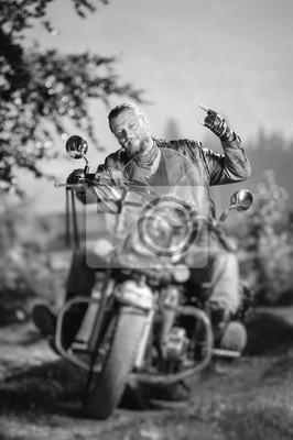 Apuesto motociclista con barba conduciendo su moto crucero en el bosque y dando el cuerno de diablo gesto y smilling. El hombre lleva chaqueta de cuero y vaqueros. Efecto de desenfoque de la lente de