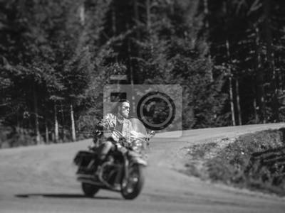 Apuesto motociclista con barba conducir su motocicleta crucero por carretera agradable en el bosque. El hombre lleva chaqueta de cuero, vaqueros y gafas de sol. Efecto de desenfoque de la lente de cam