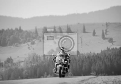 Apuesto motociclista en gafas de sol en carretera montañosa, el hombre está montando su moto de viaje personalizado. Día soleado en las montañas. Efecto suave de cambio de inclinación. En blanco y neg