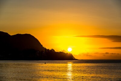 Atardecer en Mahe en Seychelles con el sol detrás de una montaña en el mar
