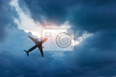 Avión en el cielo azul oscuro y la nube en la salida del sol