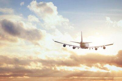 Póster avión en el cielo del atardecer