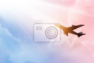 Avión en el cielo y coloridas nubes en la puesta de sol