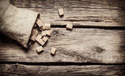 Póster Azúcar de caña refinado en la bolsa. Sobre fondo de madera.