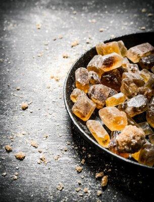 Póster Azúcar morena cristalina. En el fondo rústico negro.
