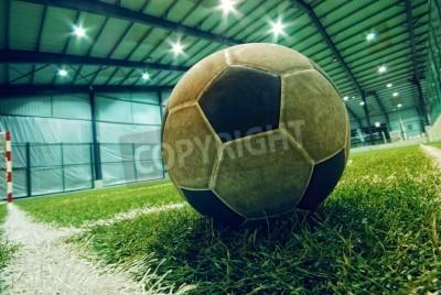 Póster balón de fútbol en la hierba verde en una zona infantil de juegos