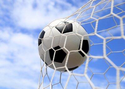 Póster balón de fútbol en la red en el cielo azul