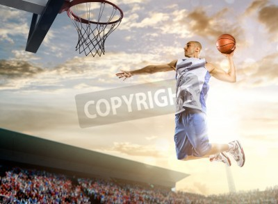 Póster Basketball player in action on background of sky and crowd