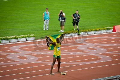 Póster Beijing - Aug 16: Usain Bolt celebrates holding the Jamaican flag after setting new world 100 meter record  for men