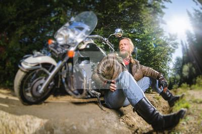 Biker barbudo posando con su moto de crucero por encargo elegante brillante. Biker está sentado en el suelo cerca de su bicicleta con chaqueta de cuero, guantes de cuero y botas de cuero. Efecto suave
