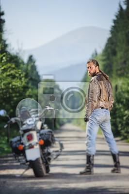 Biker con el pelo largo vistiendo chaqueta de cuero blue jeans botas y guantes de pie cerca de su motocicleta crucero en el camino abierto. Mirando a la cámara. Vista desde la parte posterior. Efecto