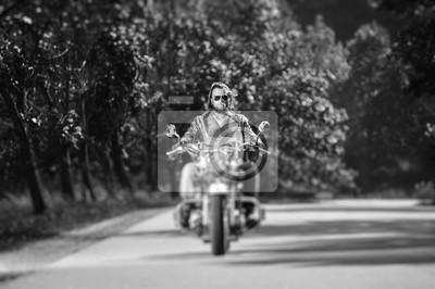 Biker con el pelo largo y la barba en gafas de sol y la chaqueta de cuero que conduce en la carretera. Efecto de desenfoque de la lente de cambio de inclinación. En blanco y negro