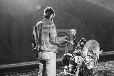 Biker de pelo largo de pie cerca de su motocicleta de crucero hecho a medida, vistiendo chaqueta de cuero y pantalones vaqueros. Mirando a la distancia. Disparo desde la parte posterior. En blanco y n